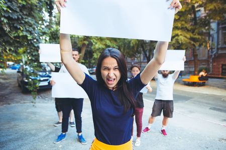 Group of protesting young people outdoors. The protest, people, demonstration, democracy, fight, rights, protesting concept. The caucasian men and womem holding empty posters or banners with copy space Stock Photo