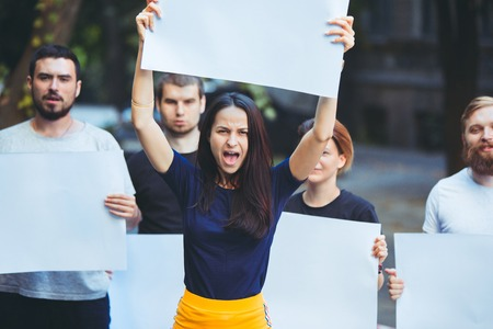 Group of protesting young people outdoors. The protest, people, demonstration, democracy, fight, rights, protesting concept. The caucasian men and womem holding empty posters or banners with copy space Banque d'images