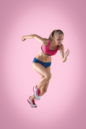 The studio shot of high jump athlete or fit woman in action i on pink background Banco de Imagens