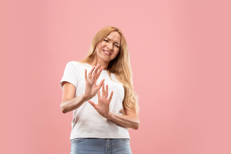 Reject, rejection, doubt concept. Doubtful woman with thoughtful expression making choice. Young emotional woman. Human emotions, facial expression concept. Front . Studio. Isolated on trendy pink Фото со стока