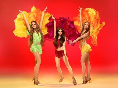 The group of young beautiful female dancers with carnival feather and fringe posing on studio background