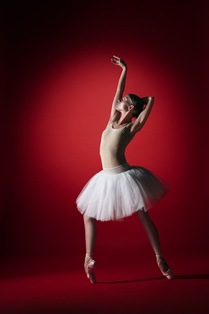 Young graceful female ballet dancer or classic ballerina dancing at red studio. Caucasian model on pointe shoes