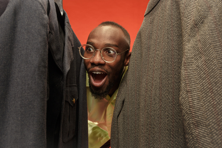 Handsome african surprised man with beard choosing shirt in a shop. Concept of shopping and lifestyle. Human emotions concepts Foto de archivo - 107284526