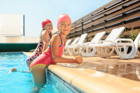 The portrait of happy smiling beautiful teen girls at the swimming pool. Little child at blue wate. Pool, leisure, swimming, summer, recreation, healthy lifstyle concept
