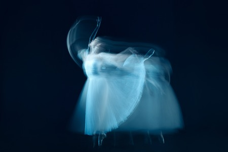 The photo as art - a sensual and emotional dance of beautiful ballerina through the veil on a dark background. A stroboscopic image of the one model Stock Photo - 107451001