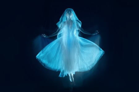 The photo as art - a sensual and emotional dance of beautiful ballerina through the veil on a dark background. A stroboscopic image of the one model