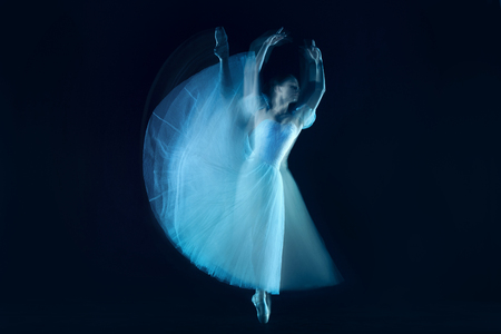The photo as art - a sensual and emotional dance of beautiful ballerina through the veil on a dark background. A stroboscopic image of the one model Stock Photo - 107498018