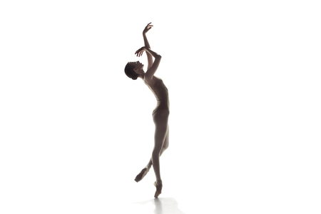 Young graceful female ballet dancer or classic ballerina dancing isolated on white studio. Caucasian model on pointe shoes Stock Photo
