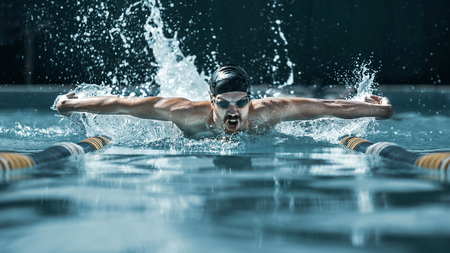 The dynamic and fit swimmer in cap breathing performing the butterfly stroke at pool. The young man. The fitsport, swimmer, pool, healthy, lifestyle, competition, training, athlete, energy concept Stock fotó