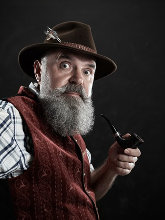 dramatic portrait of gray bearded surprised senior man in hat smoking tobacco pipe. view of Austrian, Tyrolean, Bavarian old man in national traditional costume in retro style. Stock Photo