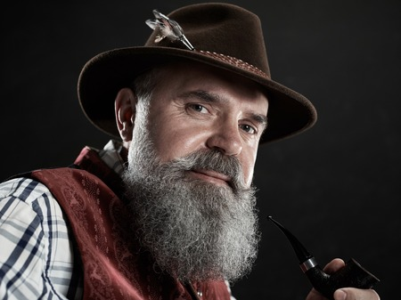 dramatic portrait of gray bearded smiling senior man in hat smoking tobacco pipe. view of Austrian, Tyrolean, Bavarian old man in national traditional costume in retro style. Stock Photo
