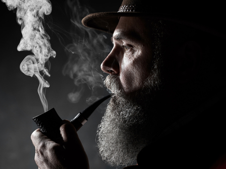 dramatic portrait of senior man in hat smoking tobacco pipe. Profile view of Austrian, Tyrolean, Bavarian old man Stock Photo