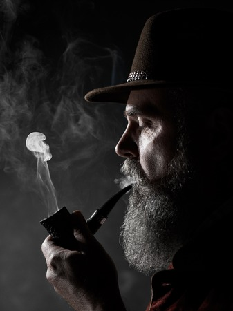 dramatic portrait of senior man in hat smoking tobacco pipe. Profile view of Austrian, Tyrolean, Bavarian old man Stock fotó