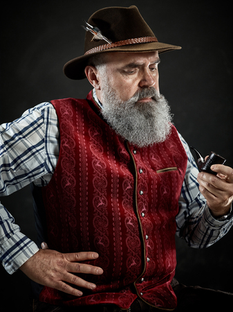 dramatic portrait of gray bearded senior man in hat smoking tobacco pipe. view of Austrian, Tyrolean, Bavarian old man in national traditional costume in retro style.