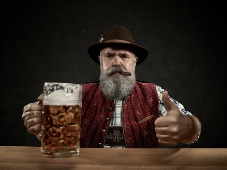 Allemagne, Bavière, Haute-Bavière. L'homme souriant avec de la bière vêtu d'un costume traditionnel autrichien ou bavarois en chapeau tenant une chope de bière au studio