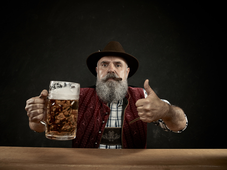 Germany, Bavaria, Upper Bavaria. The smiling man with beer dressed in in traditional Austrian or Bavarian costume in hat holding mug of beer at studio 스톡 콘텐츠