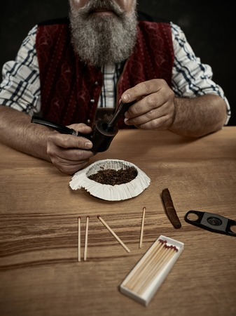 The senior bearded man sitting at table and clogging the tobacco in pipe. The male hands close up. Bavaria. a man dressed in traditional Bavarian or Austrian national traditional costume Stock Photo
