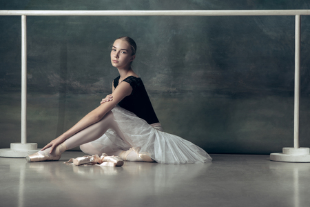 The classic ballet dancer in white tutu posing at ballet barre on studio background. Young teen before dancing. Ballerina project with caucasian model. The ballet, dance, art, contemporary, choreography concept