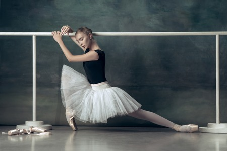 The classic ballet dancer in white tutu posing at ballet barre on studio background. Young teen before dancing. Ballerina project with caucasian model. The ballet, dance, art, contemporary, choreography concept 스톡 콘텐츠 - 107776396