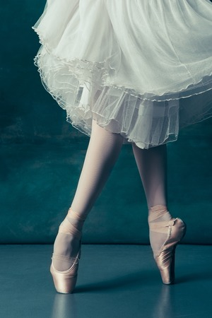 Close-up classic ballerinas legs in pointes on the gray wooden floor. Ballerina project with caucasian model. The ballet, dance, art, contemporary, choreography concept