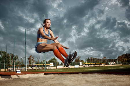Female athlete performing a long jump during a competition at stadium. The jump, athlete, action, motion, sport, success, championship concept Banque d'images - 107776812