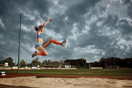 Athlète féminine effectuant un saut en longueur lors d'une compétition au stade. Le saut, l'athlète, l'action, le mouvement, le sport, le succès, le concept de championnat