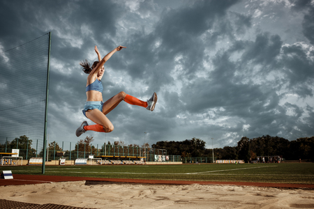 Female athlete performing a long jump during a competition at stadium. The jump, athlete, action, motion, sport, success, championship concept 스톡 콘텐츠 - 107776813