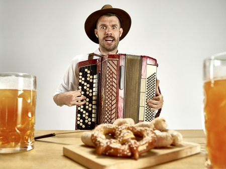 Man in traditional bavarian clothes playing accordion. Germany, Bavaria, Upper Bavaria. The young happy smiling man in traditional Austrian or Bavarian costume at pub or studio. The celebration, oktoberfest, festival concept 版權商用圖片