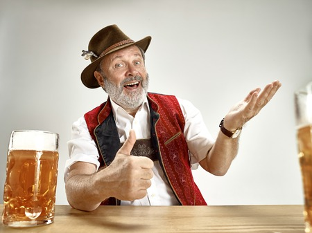Germany, Bavaria, Upper Bavaria. The senior happy smiling man with beer dressed in traditional Austrian or Bavarian costume with beer at pub or studio. The celebration, oktoberfest, festival concept