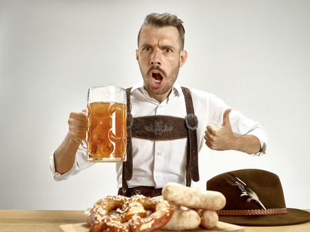 Germany, Bavaria, Upper Bavaria. The young happy smiling man with beer dressed in traditional Austrian or Bavarian costume holding mug of beer at pub or studio. The celebration, oktoberfest, festival concept Stock Photo