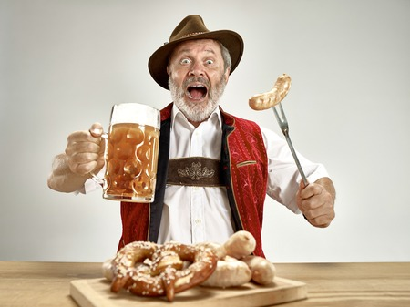 Germany, Bavaria, Upper Bavaria. The senior happy smiling man with beer dressed in traditional Austrian or Bavarian costume holding mug of beer at pub or studio. The celebration, oktoberfest, festival concept