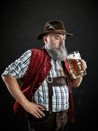 Germany, Bavaria, Upper Bavaria. The smiling man with beer dressed in in traditional Austrian or Bavarian costume in hat holding mug of beer at studio Stock Photo