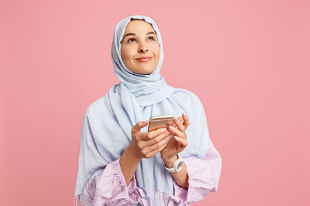 Happy arab woman in hijab with mobile phone. Portrait of smiling girl, posing at pink studio background. Young emotional woman. The human emotions, facial expression concept. Front view. 写真素材