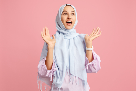 Happy surprised arab woman in hijab. Portrait of smiling girl, posing at pink studio background. Young emotional woman. The human emotions, facial expression concept. Front view. Archivio Fotografico
