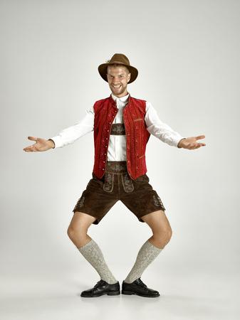 Ritratto di Oktoberfest giovane uomo in cappello, indossando un tradizionale bavarese vestiti in piedi a figura intera in studio. La celebrazione, l'oktoberfest, il concetto di festival