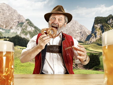 Germany, Bavaria. The senior happy smiling man with beer dressed in traditional Austrian or Bavarian costume with Bavarian pretzels against Alpine mountain landscape. oktoberfest, festival concept Stock Photo