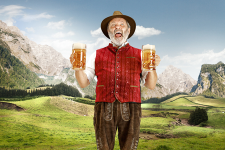 Germany, Bavaria. The senior happy singing man with beer dressed in traditional Austrian or Bavarian costume against Alpine mountain landscape. oktoberfest, festival concept