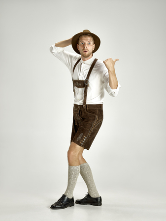 Portrait of Oktoberfest young man in hat, wearing a traditional Bavarian clothes standing at full-length at studio. The celebration, oktoberfest, festival concept