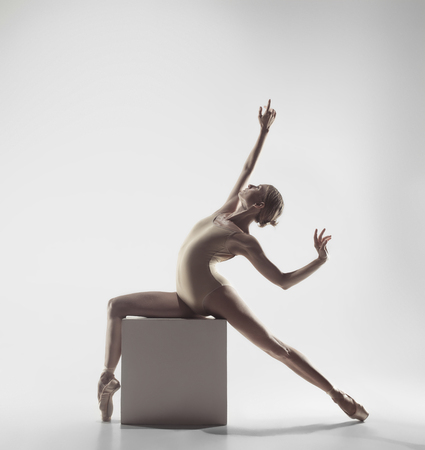 Young graceful female ballet dancer or classic ballerina dancing on white studio. Caucasian model on pointe shoes