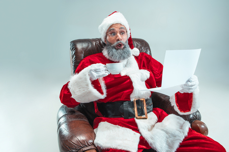 Funny serious guy with christmas hat sitting at studio with a letter of desire. New Year Holiday. Christmas, x-mas, winter, gifts concept. Man wearing Santa Claus costume on gray. Copy space. Winter sales.
