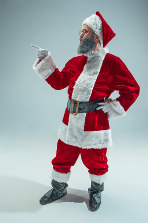 Funny guy with christmas hat posing at studio pointing to left. New Year Holiday. Christmas, x-mas, winter, gifts concept. Man wearing Santa Claus costume on gray. Copy space. Winter sales. 免版税图像