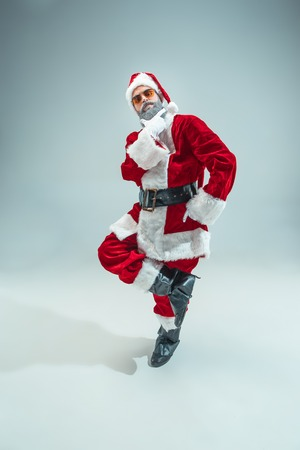 Funny serious guy with christmas hat posing at studio. New Year Holiday. Christmas, x-mas, winter, gifts concept. Man wearing Santa Claus costume on gray. Copy space. Winter sales.