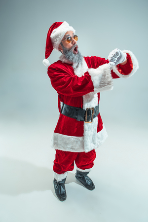 Funny surprised guy with christmas hat posing at studio. New Year Holiday. Christmas, x-mas, winter, gifts concept. Man wearing Santa Claus costume on gray. Copy space. Winter sales.