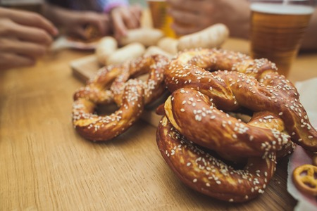 Gekookte witte worst, geserveerd met bier en pretzels. Perfect voor het Oktoberfeest. Natuurlijke houten achtergrond. Vooraanzicht. Stockfoto