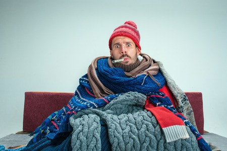 Homme malade barbu avec cheminée assis sur un canapé à la maison ou en studio avec thermomètre recouvert de vêtements chauds tricotés. Maladie, concept de grippe. Détente à la maison. Concepts de santé. Banque d'images