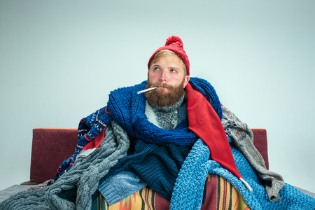 Bearded sick man with flue sitting on sofa at home or studio covered with knitted warm clothes. Illness, influenza concept. Relaxation at Home. Healthcare Concepts.