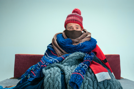 Bearded sick man with flue sitting on sofa at home or studio covered with knitted warm clothes. Illness, influenza, pain concept. Relaxation at Home. Healthcare Concepts.