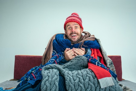Bearded sick happy man with flue sitting on sofa at home or studio covered with knitted warm clothes. Illness, influenza concept. Relaxation at Home. Healthcare Concepts.
