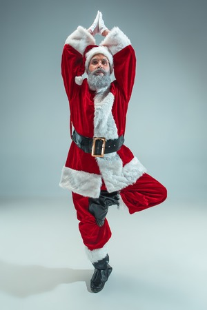 Funny serious guy with christmas hat sitting at yoga pose at studio. New Year Holiday. Christmas, x-mas, winter, gifts concept. Man wearing Santa Claus costume on gray. Copy space. Winter sales. 免版税图像