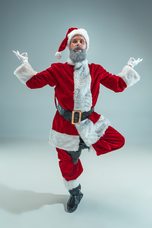 Funny serious guy with christmas hat sitting at yoga pose at studio. New Year Holiday. Christmas, x-mas, winter, gifts concept. Man wearing Santa Claus costume on gray. Copy space. Winter sales. Stock Photo